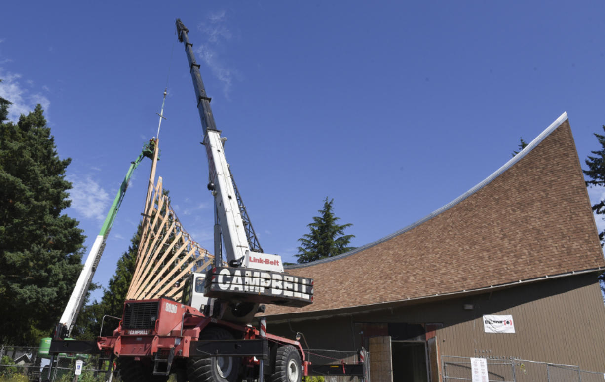 A crane holds a cross over the roof of First Congregational United Church of Christ in Hazel Dell while workers in a construction basket secure it into place.