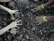 Indian women pick reusable pieces from heaps of used coal discarded by a carbon factory in Gauhati, India.