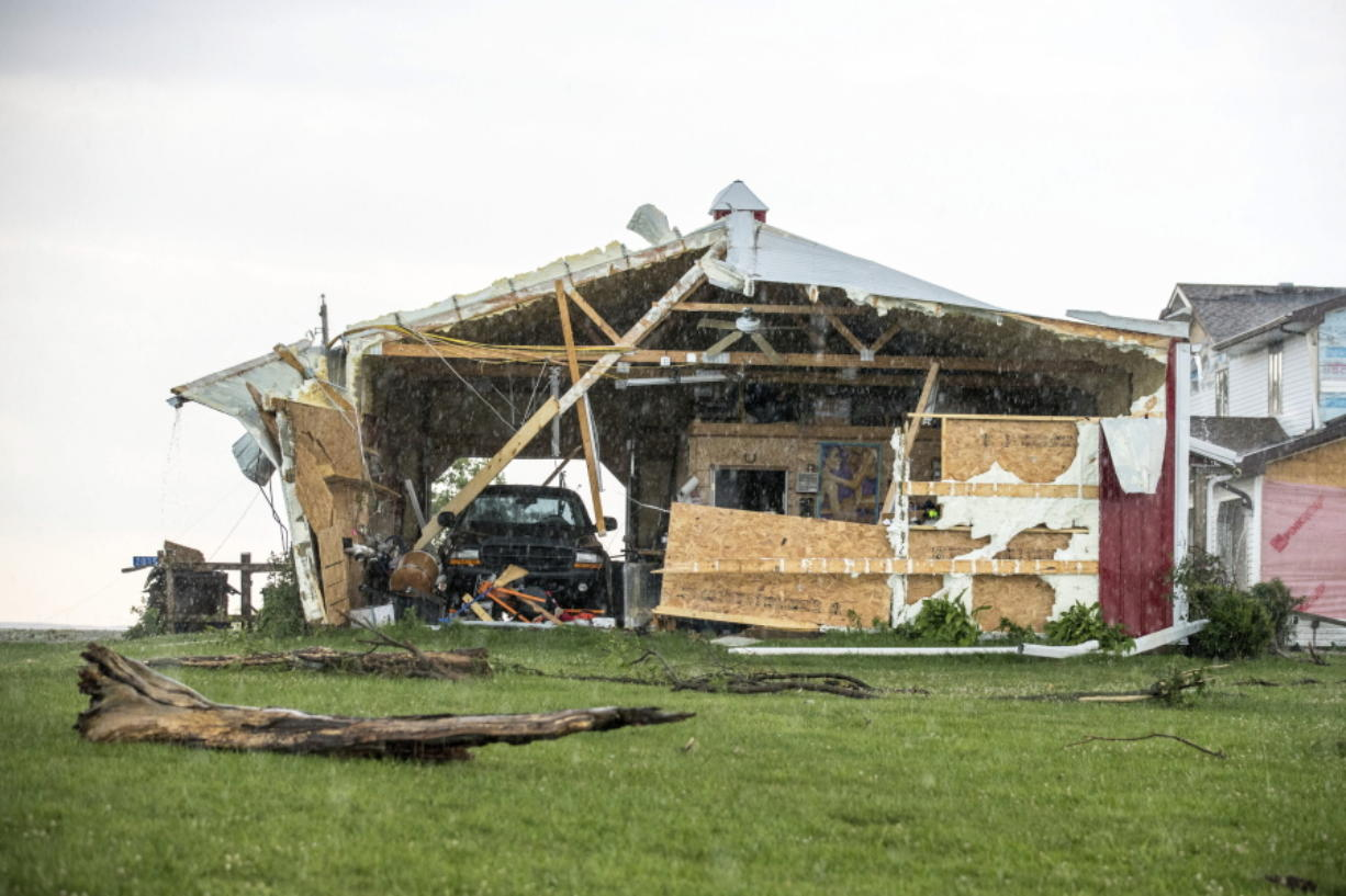 In this Wednesday, June 28, 2017 photo, a car sits in a garage, damaged after a tornado hit the property of Dee and Lynn Ossian in Farragut, Iowa.