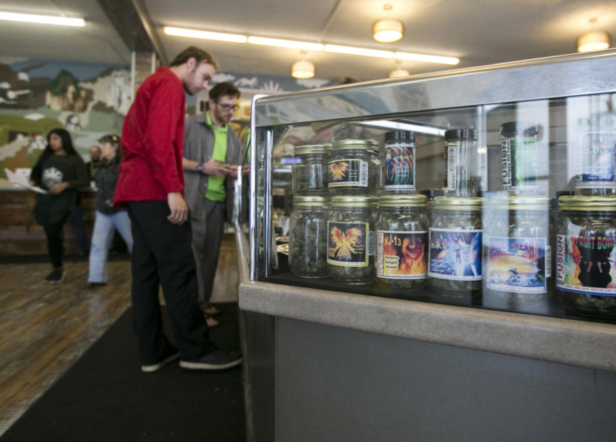 Customers peruse products in a case at Main Street Marijuana in downtown Vancouver. The city's portion of the marijuana taxes will go toward law enforcement.