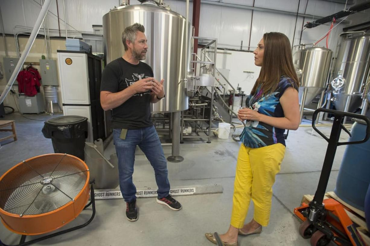 Jeff Seibel, co-owner of Ghost Runners Brewery, left, chats with U.S. Rep. Jaime Herrera Beutler at Ghost Runners Brewery on Thursday. A bill co-sponsored by the Camas republican would cut federal excise taxes paid by the breweries.