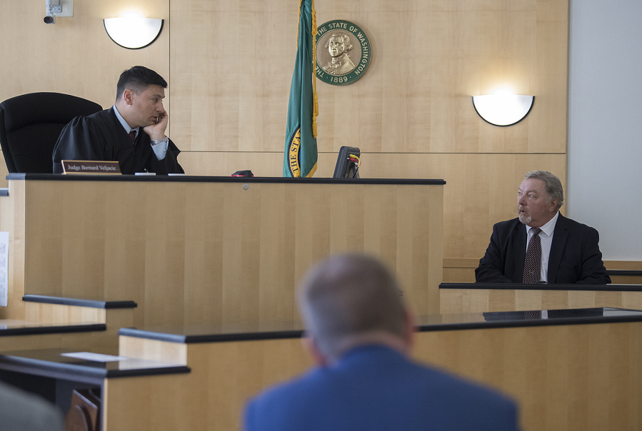 Judge Bernard Veljacic, left, talks with John Jones, a contract security company manager, as he testifies in an evidentiary hearing in a public records lawsuit on Monday morning. Veljacic ruled in favor of releasing footage from jail surveillance cameras that captured the incident that led to the 2015 death of Mycheal Lynch, an inmate at the jail.