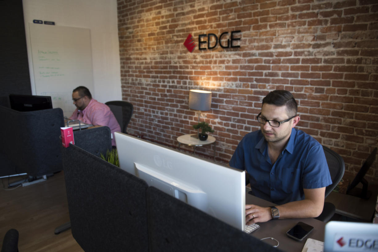 Josh McKinney, chief technology officer at Edge Networks, left, and President Mark Tishenko work at the downtown Vancouver office. The company has seen revenues rise 20 percent since offering an on-call cybersecurity service.