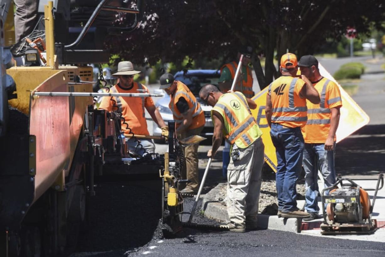 A crew from Lakeside Industries paves Southeast Norelius Drive at the intersection of Southeast 150th Avenue on Wednesday. The work is part of a new effort by Vancouver to repair failing residential streets.