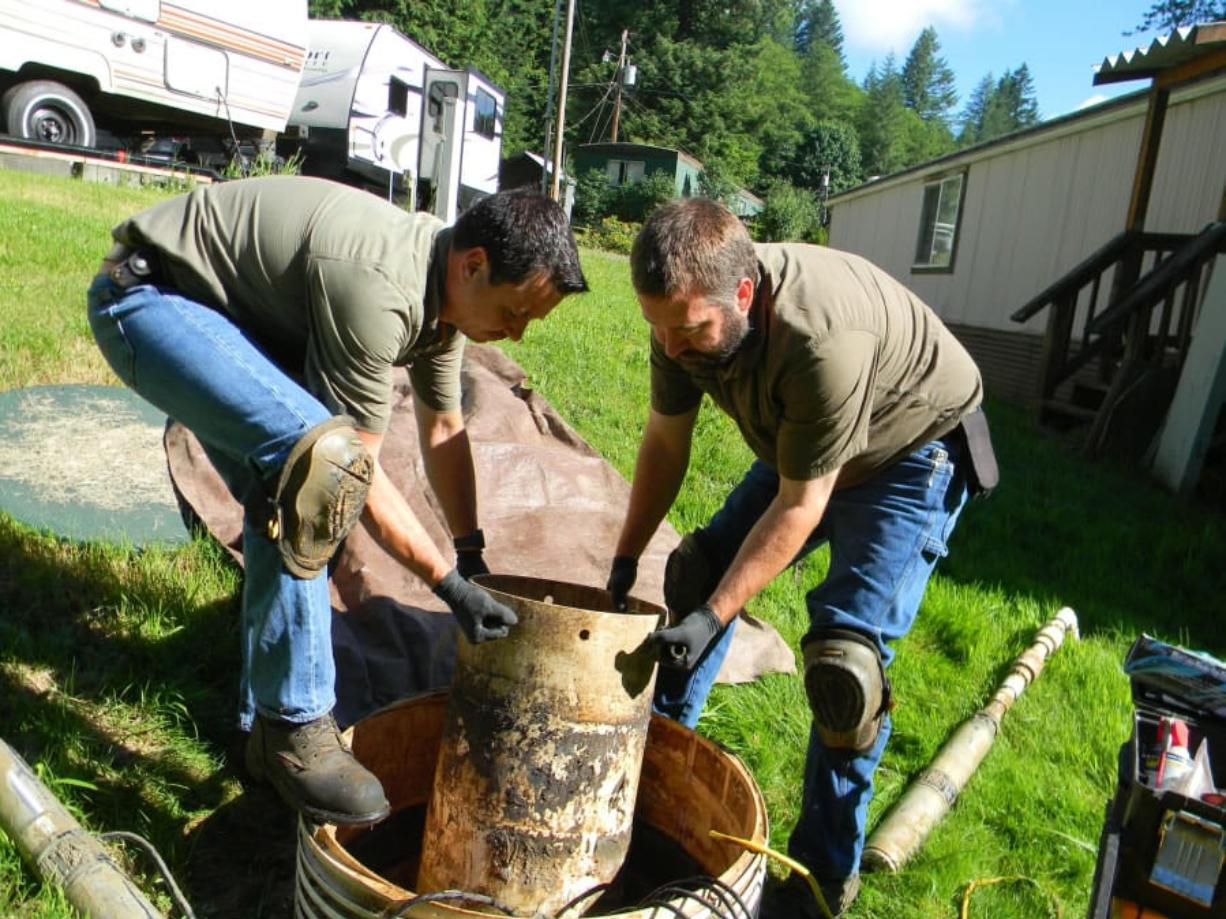 Ronnie Tamez, the owner of First Call Septic Service, and Chris Gross, a technician, pull the pump out of a septic system in a mobile home park in north Clark County. If something isn't working, the pump will set off alarms, to the annoyance of the park's residents.