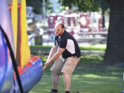 Ian Manheimer, owner of Bounce-N-Battle Inflatable Party Rentals in Vancouver, secures a bounce house before an event at Marshall Recreation Center.