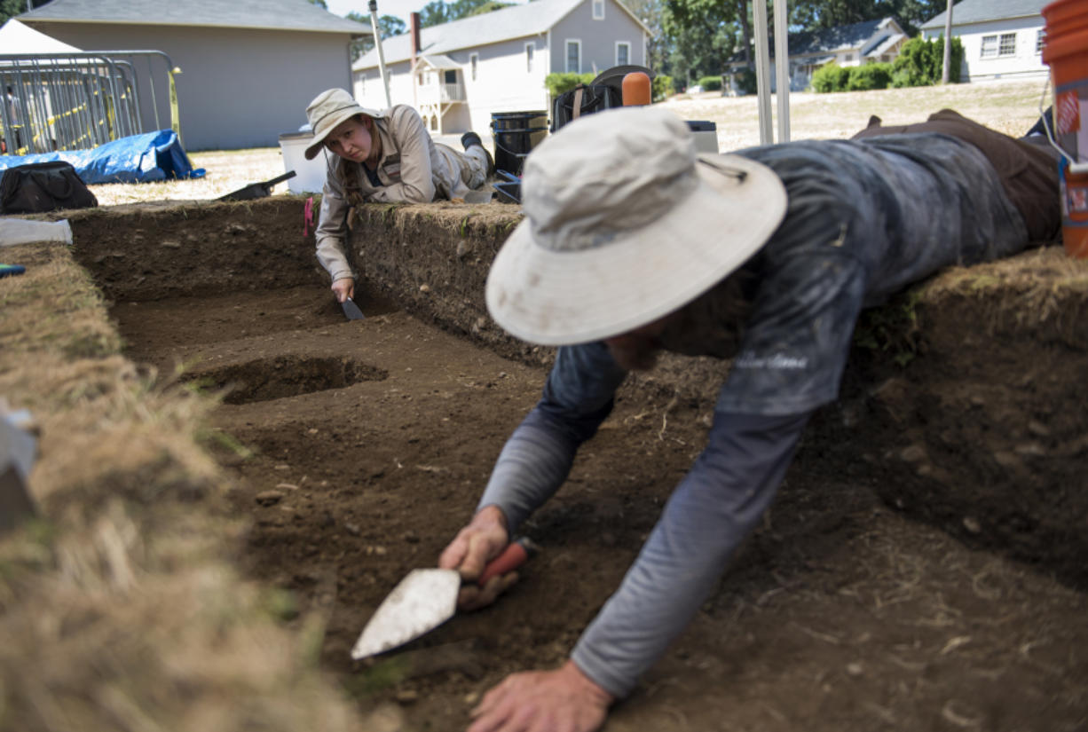 Co-field director Katie Wynia of Portland, from left, and Portland State University graduate Jesse Nelson of Portland trowel a dig site Friday during the annual archaeological summer field school on the south side of Vancouver Barracks in the Fort Vancouver National Historic Site.