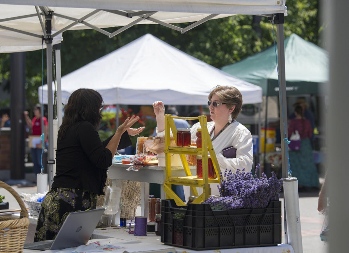 Danielle Davis, left, of Give Us A Buzz, talks with customer Rachel Belveal, who works at the Clark County Treasurer's Office, at the Franklin Street Farmers Market on Wednesday afternoon. The market debuted Wednesday and will take place every Wednesday through August.