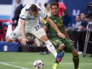 Vancouver Whitecaps defender Jake Nerwinski (28) vies for control of the ball with Portland Timbers midfielder Sebastian Blanco, right, during the first half of MLS soccer game action in Vancouver, British Columbia, Sunday, July, 23, 2017.