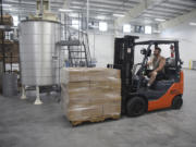 Erick Stewart, floor supervisor at Northwest Adhesives, uses a forklift to transport a wax pallet at the company's headquarters in Washougal.