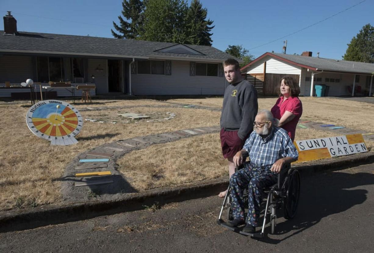 Tom Laidlaw, center; his grandson, Doug Brouhard, left; and his daughter, Debra Brouhard, look over the sundial garden Laidlaw created in his Vancouver Heights neighborhood front yard.