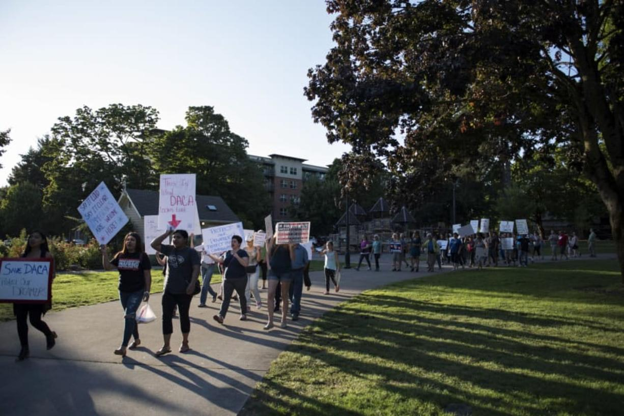 People walk through Esther Short Park during a Save DACA rally hosted by the League of United Latin American Citizens Wednesday evening in downtown Vancouver.