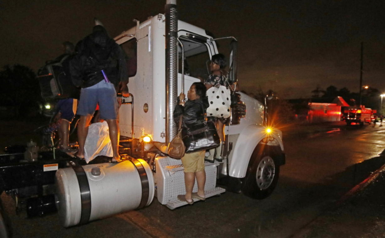 Residents cling to a commercial truck as it carries them to safety following flooding to their homes, late Monday night in Lake Charles, La. Almost constant rain over the last two days from Harvey, overcame the city's drainage system, flooding several subdivisions and necessitating home rescues. (AP Photo/Rogelio V.