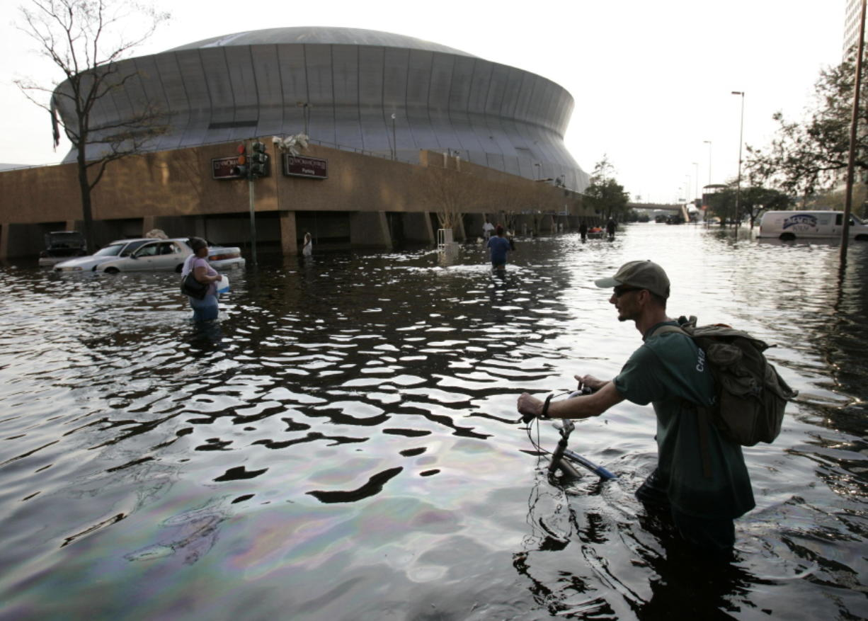 FILE - This Aug, 31, 2005, file photo shows a man pushing his bicycle through flood waters near the Superdome in New Orleans after Hurricane Katrina left much of the city under water. Some of those now taking shelter from Tropical Storm Harvey at Houston's main convention center may be having flashbacks to a previous storm. Elected officials in Texas are promising to heed the lessons from Katrina, which resulted in hundreds of deaths and tens of billions of dollars in damage.