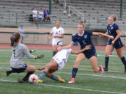 Union's MaKayla Woods, center, attempts to shoot past Gig Harbor goalkeeper Auna Havens on Thursday at McKenzie Stadium. Maddie Goss would score a few seconds later in Union's 4-1 win.