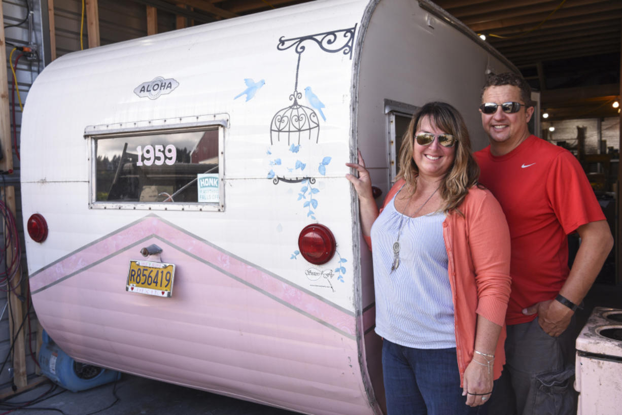 René Perret and Jeremy Ralston, owners of Down River Vintage Trailer Restoration, stand next to a 1959 Aloha trailer they're renovating in their shop in Woodland.