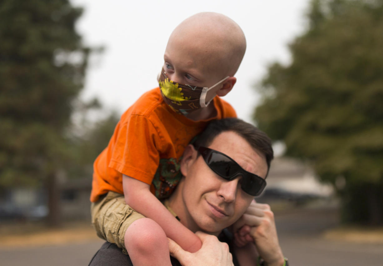 """Declan Reagan, 5, sits atop the shoulders of his father, Francis Reagan, Tuesday outside the Washougal Police Department, where his dad serves as a police officer. Declan received a bone marrow transplant in July after being diagnosed with two types of cancer. """"A woman in another country gave him the chance to have a life, and that's really cool"""" says his mother, Lauren Reagan."""
