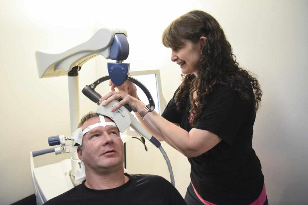 Todd Walker, 46, left, holds his head still while psychiatric nurse practitioner Ruth Rogers prepares a NeuroStar machine for transcranial magnetic stimulation Sept. 6 at Serenity TMS in Vancouver. TMS is a Food and Drug Administration-approved treatment for major depressive disorder.