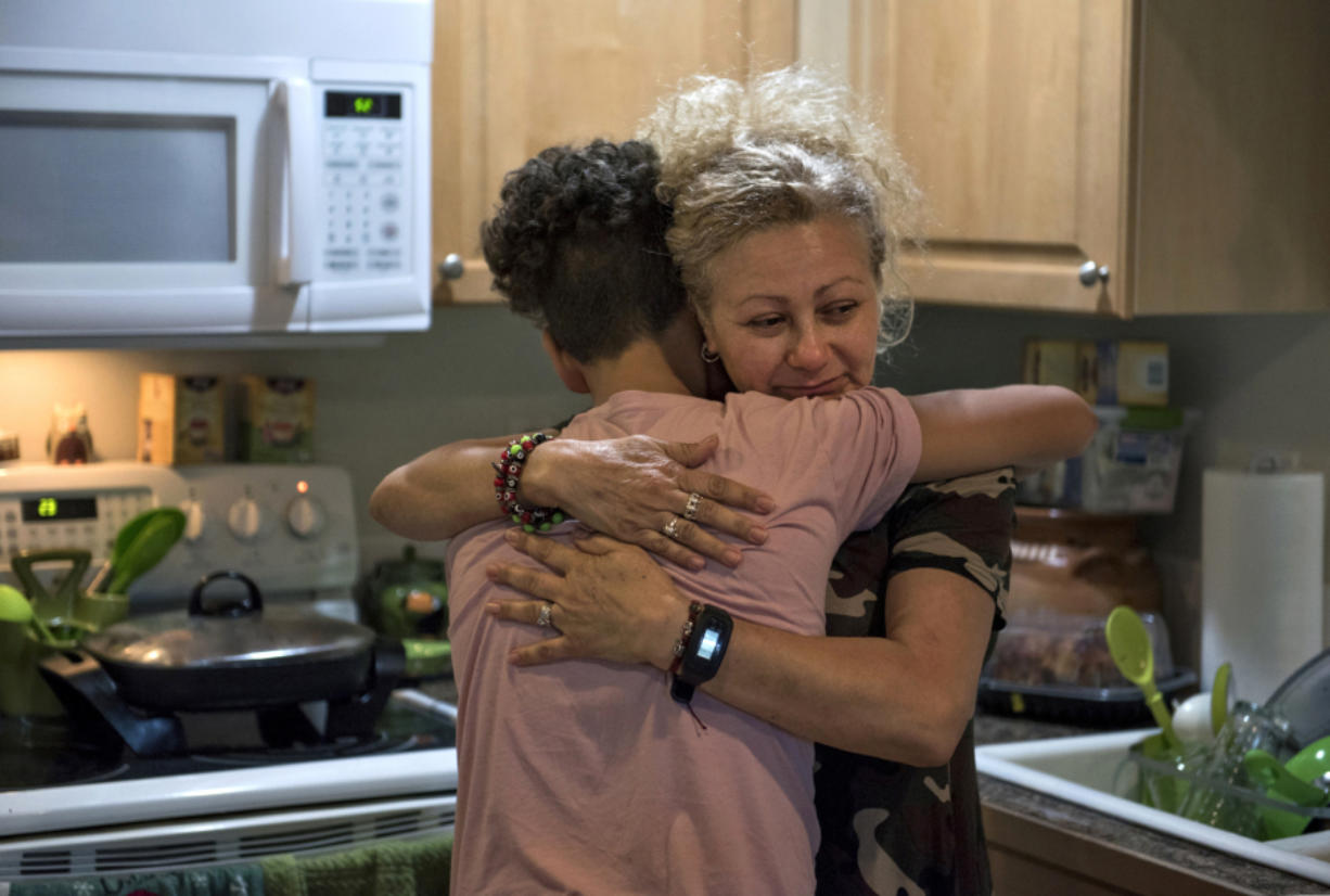 Enedis Flores, 51, hugs her 12-year-old son, Raymond, in their kitchen late this summer at their Vancouver home. The family has been struggling since their father, Ramon Flores-Garcia, was taken into custody by U.S. Immigration and Customs Enforcement agents earlier this year and was deported.