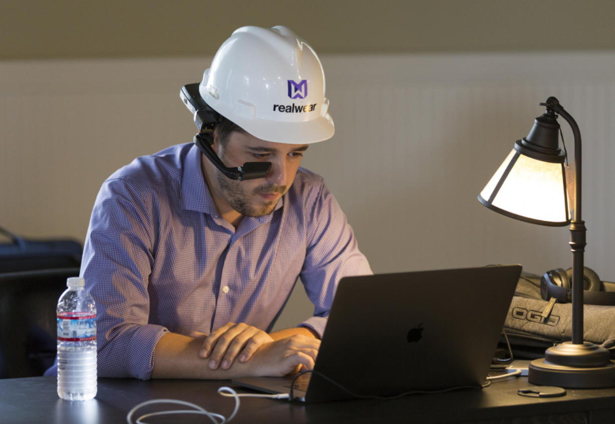 Kyle Firlik of RealWear wears the company's HMT-1 headset while working at the Fort Vancouver Artillery Barracks on Wednesday. CEO Andy Lowery said he hoped to have 200 to 300 people working there in the coming years.