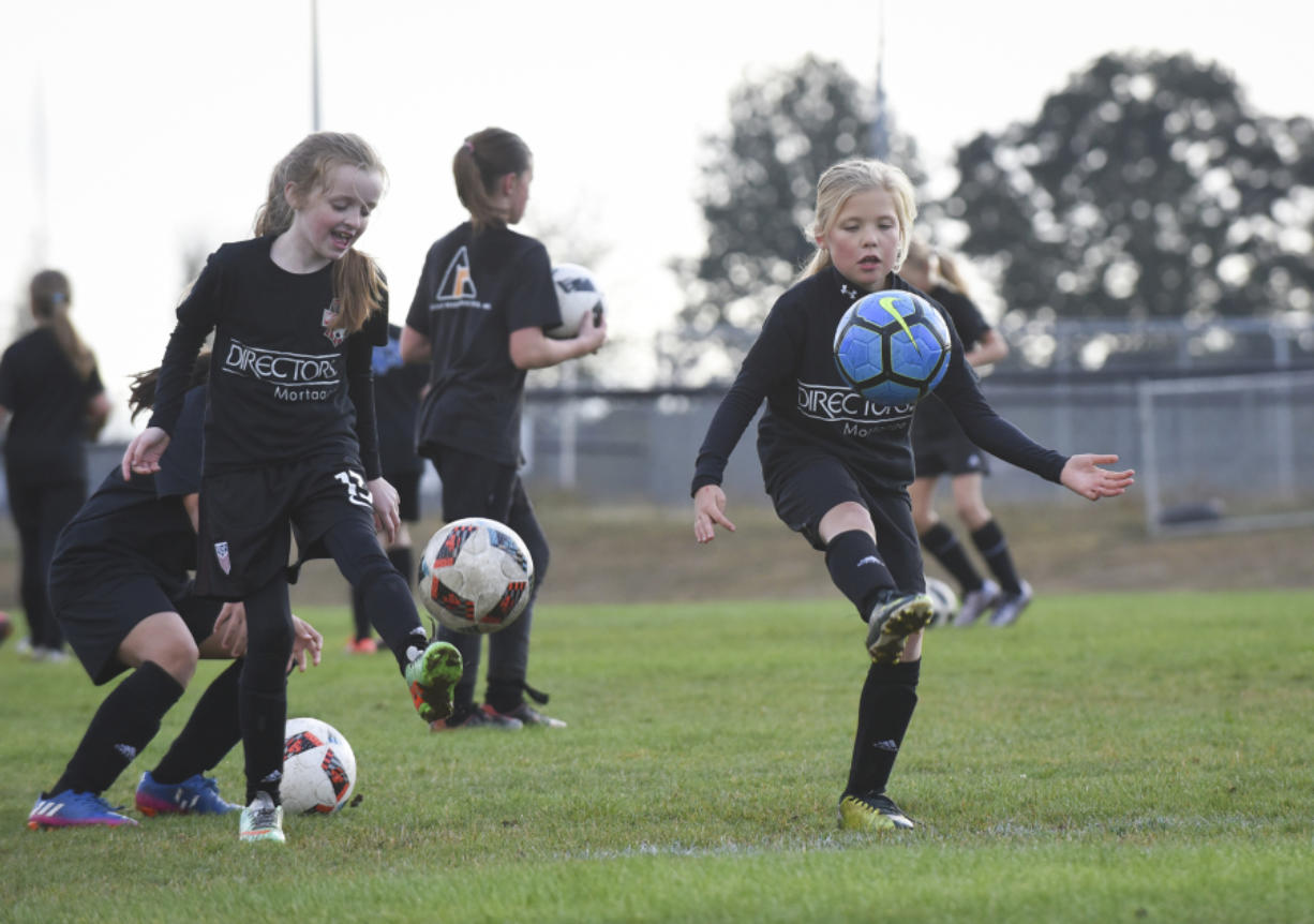 Dicey Delano, left, and Ava Bond practice with third- and fourth-grade Washington Timbers Football Club players Wednesday evening at Harmony Sports Park in the east Vancouver area.