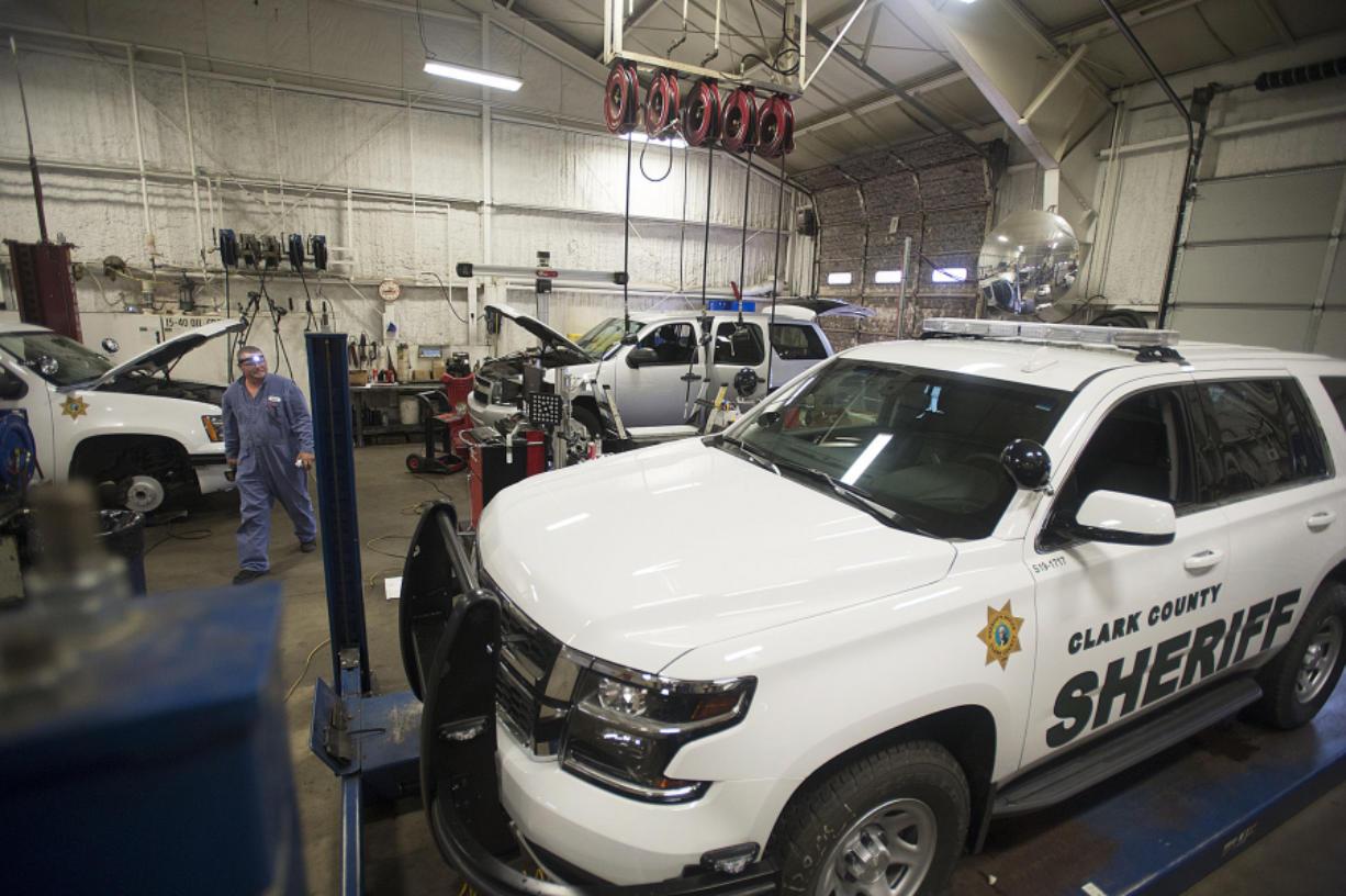Craig Callaway, a county technician, walks past sheriff's office vehicles parked at Clark County Fleet Services. Amanda Cowan/The Columbian