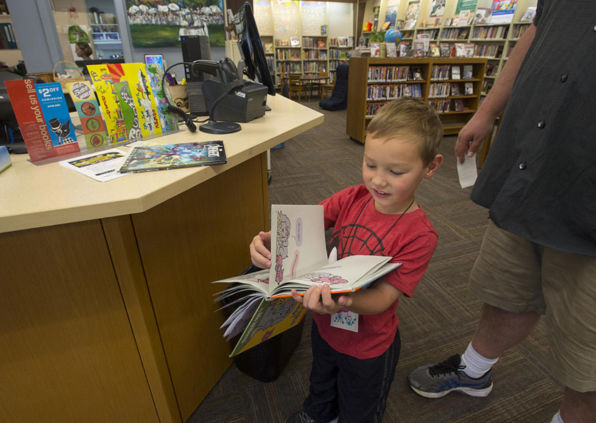 Connor Jackson, 5, of Vancouver flips through a book he checked out Friday after he and his dad, Mike, visited the Washougal Community Library. A new library would include a children's area. Staffers now must roll bookcases out of the way for story times.