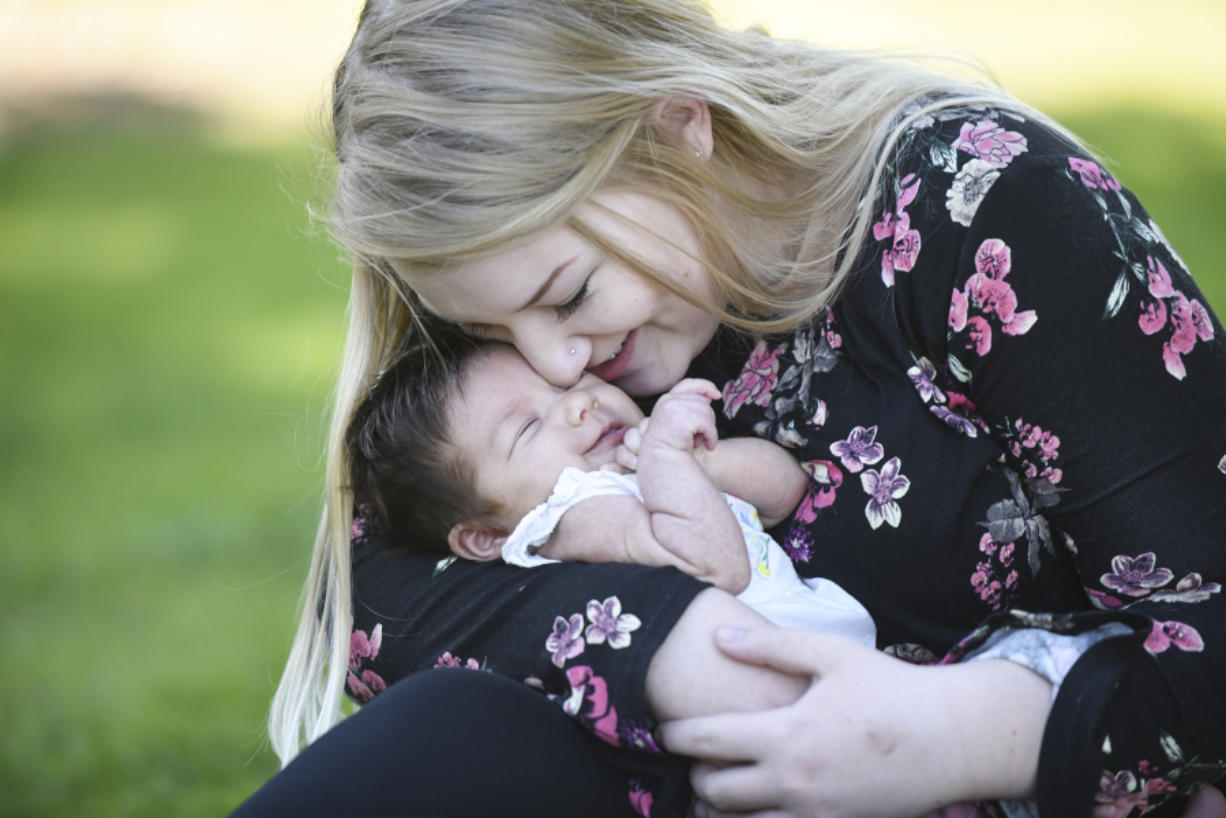 Zoe Davisson, 18, snuggles with her daughter, 7-week-old Rae Davisson, during a visit Thursday to H.B. Fuller Park in Vancouver. Davisson enrolled in the county's Nurse-Family Partnership program while pregnant. PeaceHealth Southwest Medical Center is working with the county to help sustain and expand the program for young, first-time moms.