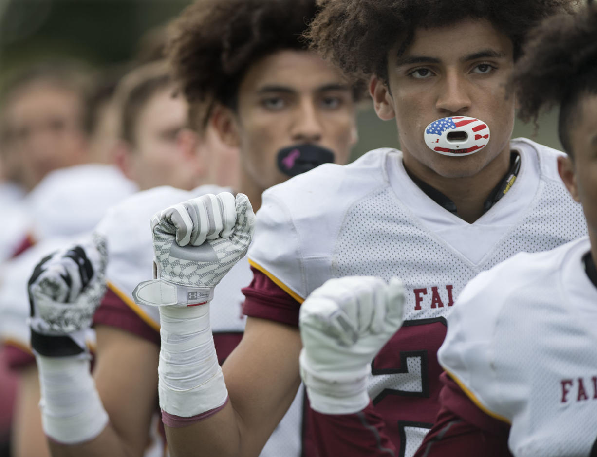 Prairie's Zeke Dixson, background, and AJ Dixson, foreground, raise their fists during the singing of the National Anthem before the game against Evergreen at McKenzie Stadium on Friday afternoon, Sept. 29, 2017.