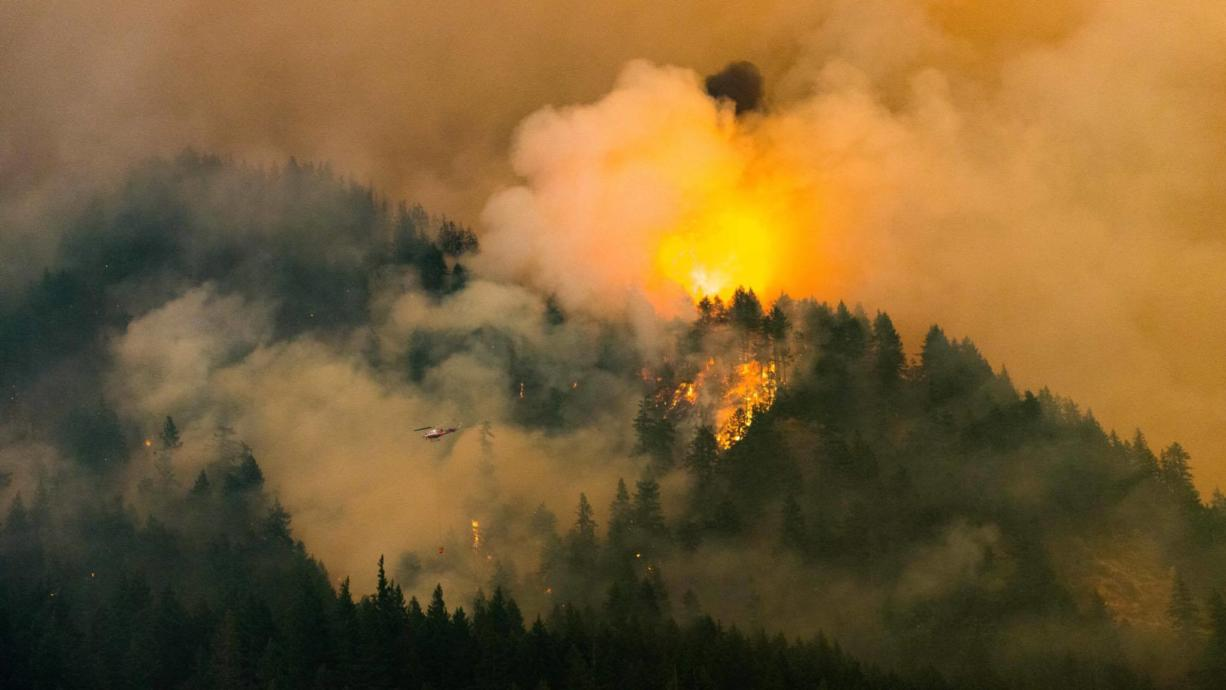 A helicopter fights the Eagle Creek Fire in Oregon on Monday as seen from the Bonneville Dam area Monday night.