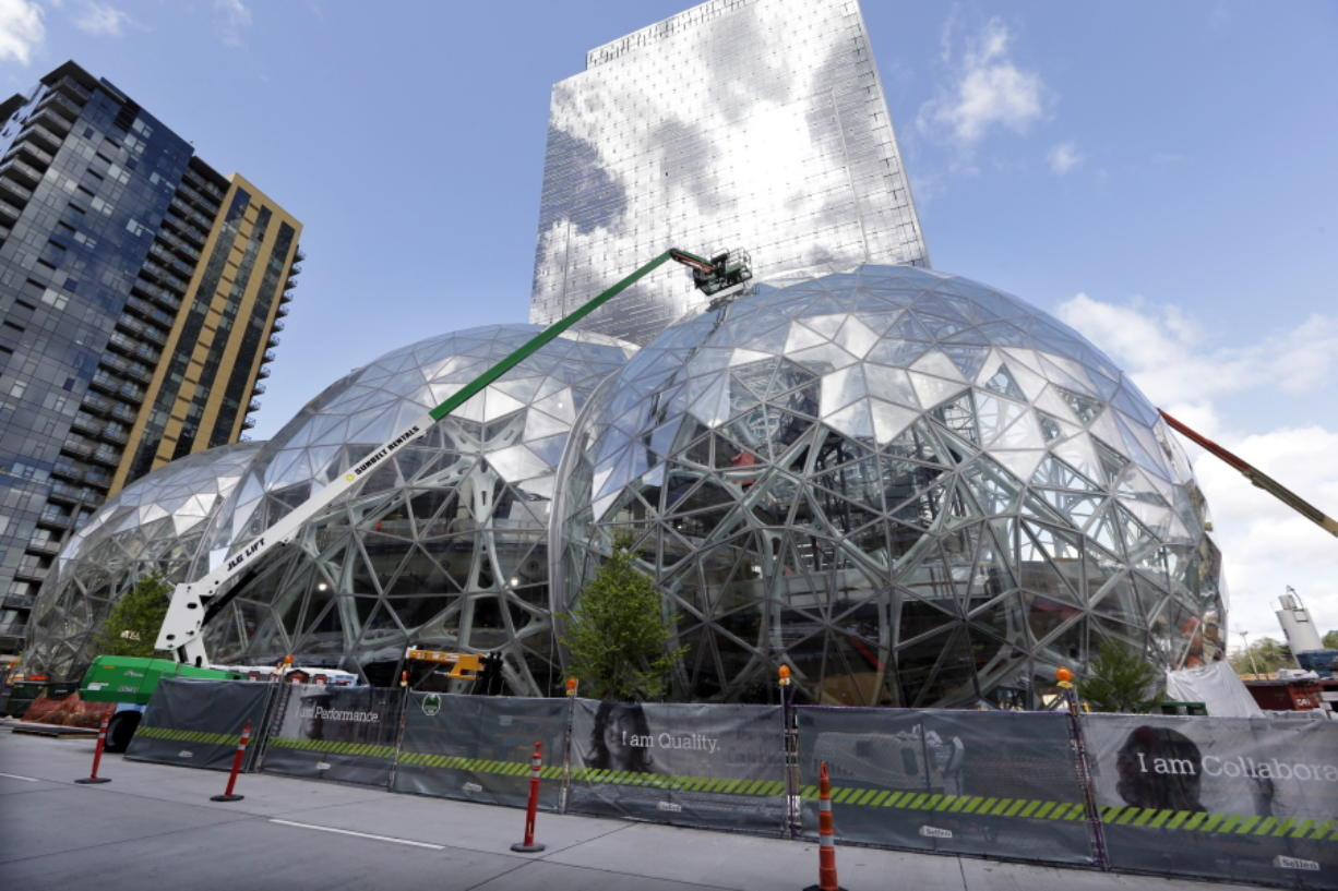 """Construction continues on three large, glass-covered domes as part of an expansion of the Amazon.com campus in downtown Seattle. Amazon said Thursday that it will spend more than $5 billion to build another headquarters in North America to house as many as 50,000 employees. It plans to stay in its sprawling Seattle headquarters and the new space will be """"a full equal"""" of its current home, said founder and CEO Jeff Bezos."""