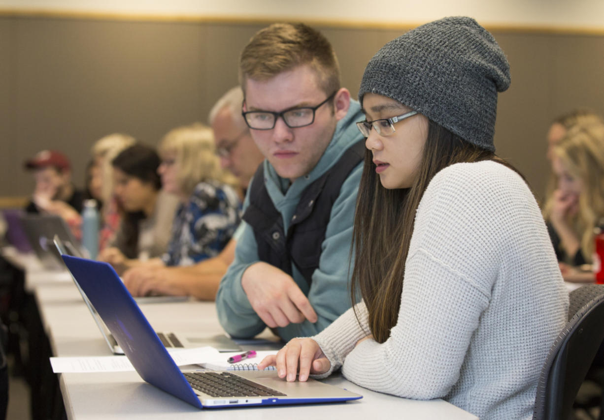 Junior Brayden Cooley, left, and senior Maciel Draculan work on a digital polarization initiative assignment at Washington State University Vancouver. (Andy Bao/The Columbian)