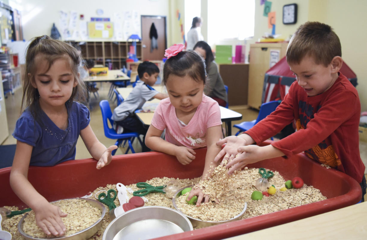 Aaralynn Marua, 4, from left, Alahoni Aguaro-Powell, 4, and Nathan Allan, 5, play with oatmeal in a blended preschool class at Hough Early Learning Center on Friday. About half the class are students with disabilities, while the other half are general education students. (Ariane Kunze/The Columbian)