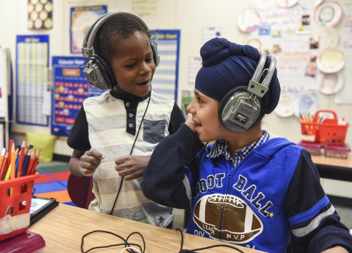 Benaiah Toussaint, 6, from Haiti and Amritpal Singh, 6, from India, sing together while working on iPads in their English language learning class for first through third grades in the Fircrest Elementary School Newcomers Program on Tuesday. Students learn English and about the United States' culture while enrolled in the program.