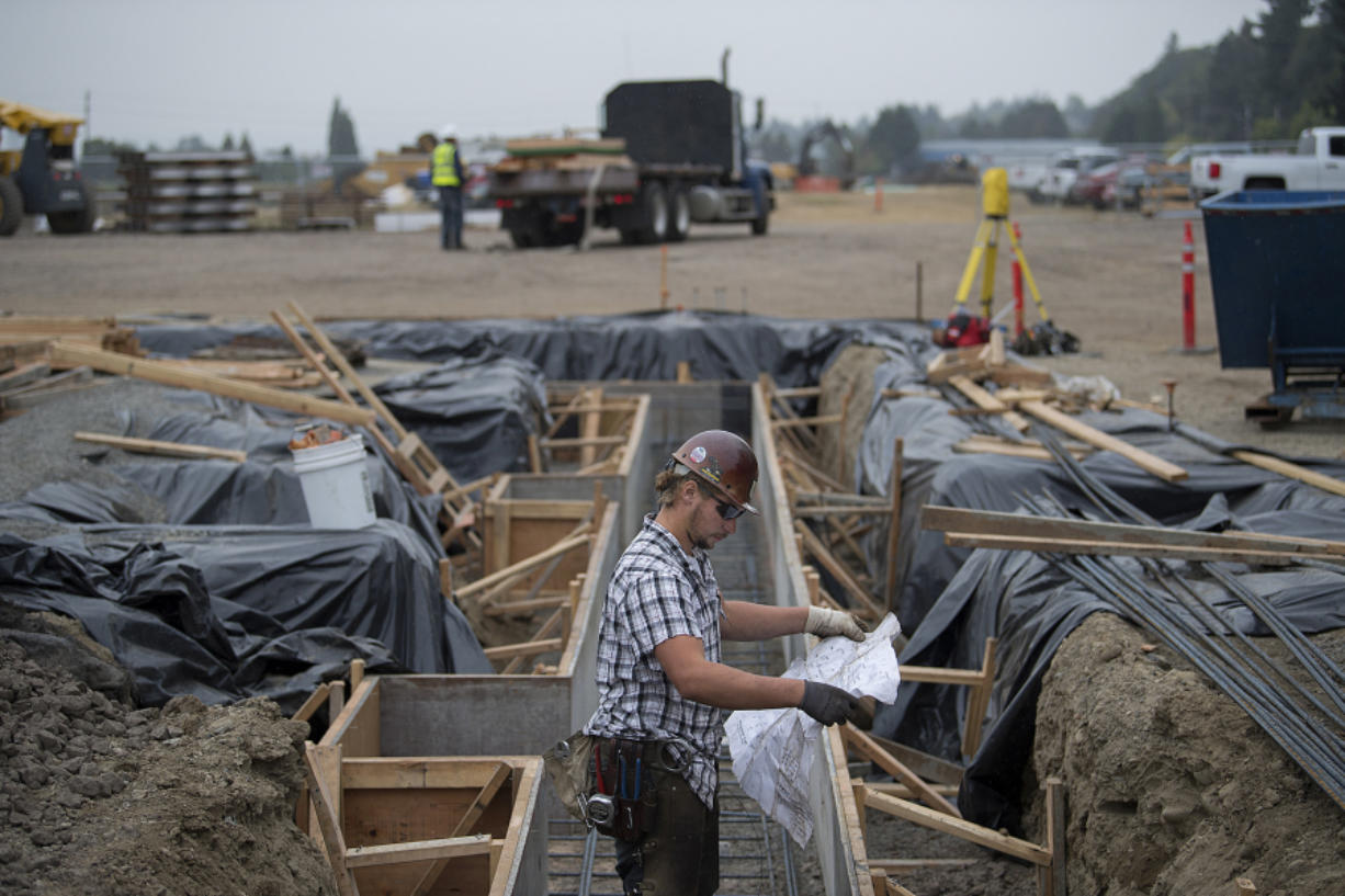 Mathew Beraldo, working for a subcontractor for Killian Pacific, looks over plans while working with colleagues to build a new office park on Columbia House Boulevard. The first phase is a 45,000-square-foot office for a tenant yet to be revealed.