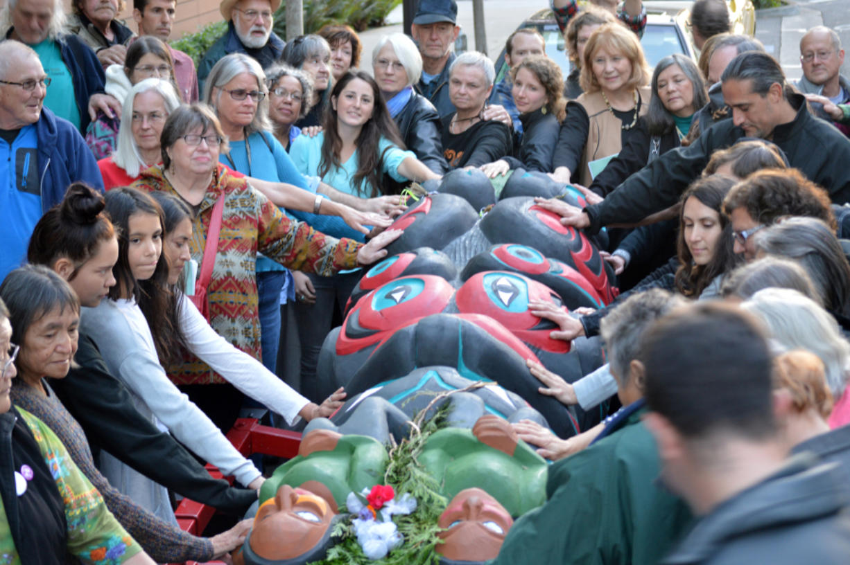 A crowd lays their hands on a totem pole bound for the Carnegie Museum of Natural History Monday evening.