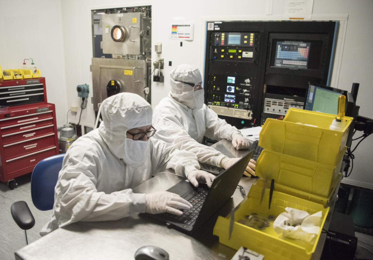 nLight technicians Carlito Gutierrez, left, and Stefan Ilchenko work from computers near an optical coding machine, pictured back left. nLight makes industrial lasers and recently signed a $1.93 million contract with the U.S. military.