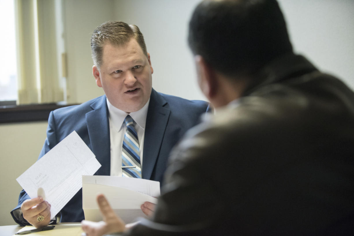 Volunteer attorney Ben Moody gives a client legal advice during a meeting at the Clark County Courthouse on Friday. Moody typically volunteers every Friday giving advice to people facing evictions. Ariane Kunze/The Columbian