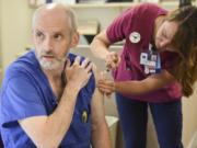 Joel Justus, a central sterile technician, receives a flu shot from Lindsey Wreden.