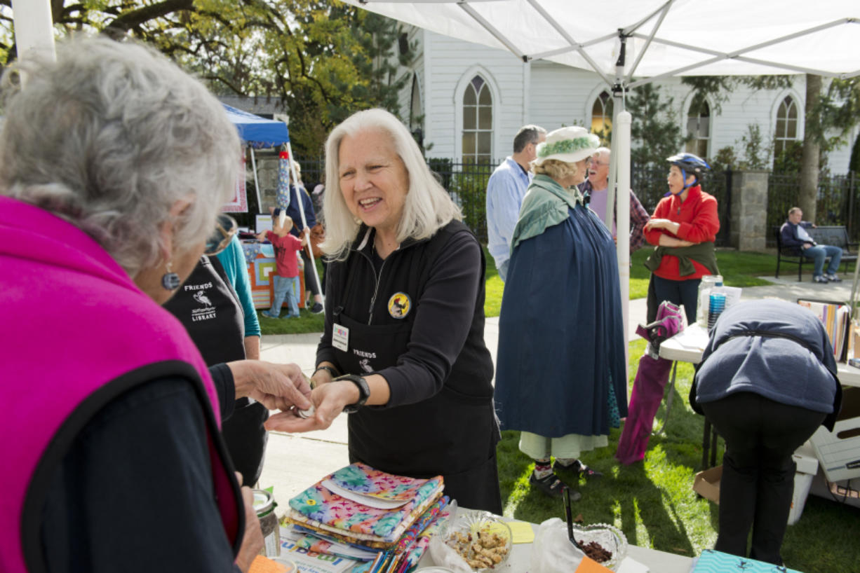 Lois Chapman, left, hands money to Jeanne Androvich, president of Friends of Ridgefield Community Library, after buying a book at a fund-raising event on Oct. 7.