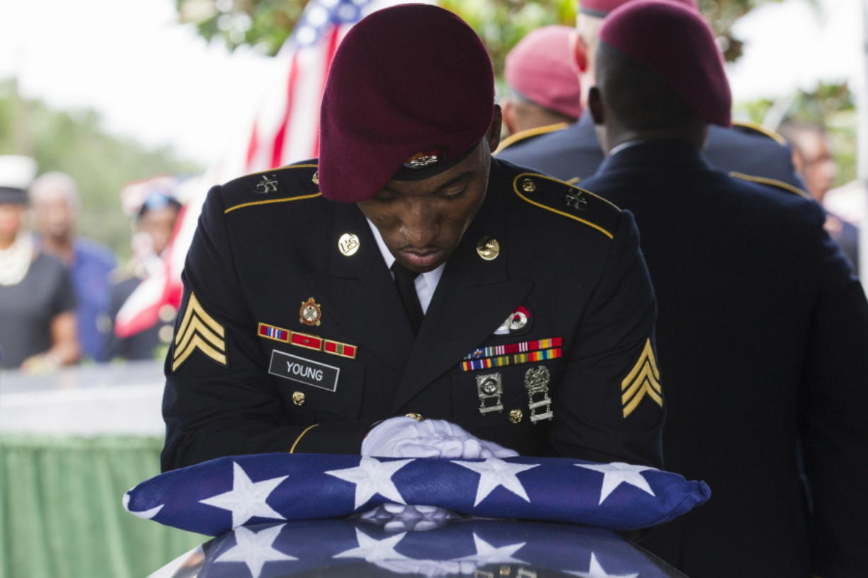 Sgt. Donald Young places a U.S. flag over the casket of Sgt. La David Johnson during his burial service at Fred Hunter's Hollywood Memorial Gardens in Hollywood, Fla., on Saturday, Oct. 21, 2017. Mourners remembered not only a U.S. soldier whose combat death in Africa led to a political fight between President Donald Trump and a Florida congresswoman but his three comrades who died with him. (Matias J.
