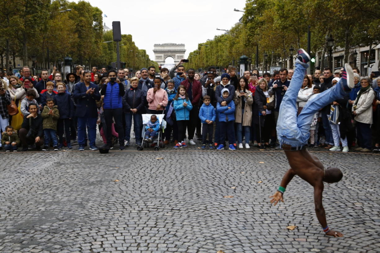 """People watch a dancer on the Champs Elysees on Oct. 1 during the """"day without cars"""" in Paris."""