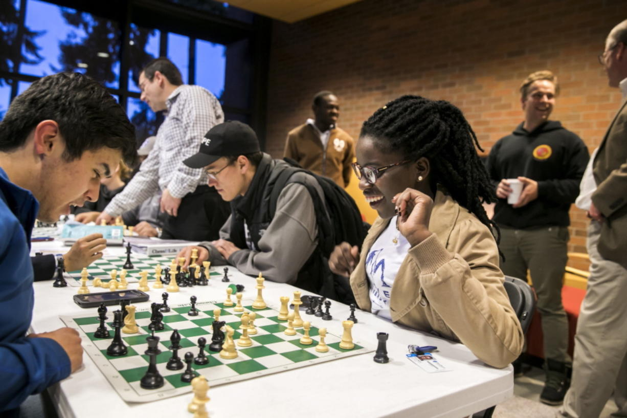 Phiona Mutesi, center, plays chess with Walter Borbridge, left, during their first chess team meeting in Kirkland.