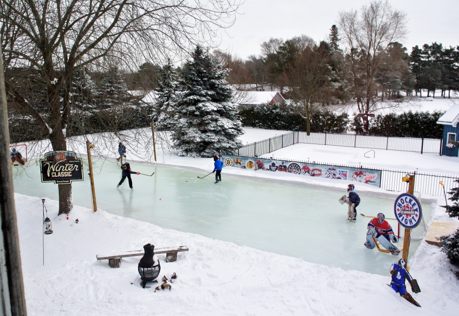 Skaters playing hockey on the Brown family's backyard ice rink in Toronto.  Brown Family/ - Backyard Hockey Rinks: From Simple To Elaborate The Columbian