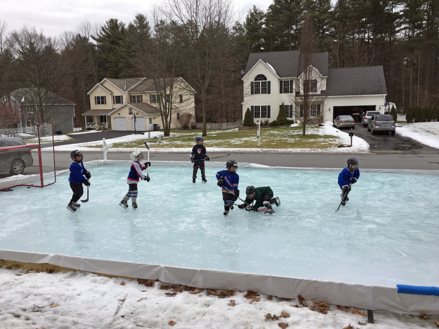 17, 2016 photo provided by Iron Sleek shows children playing hockey on - Backyard Hockey Rinks: From Simple To Elaborate The Columbian