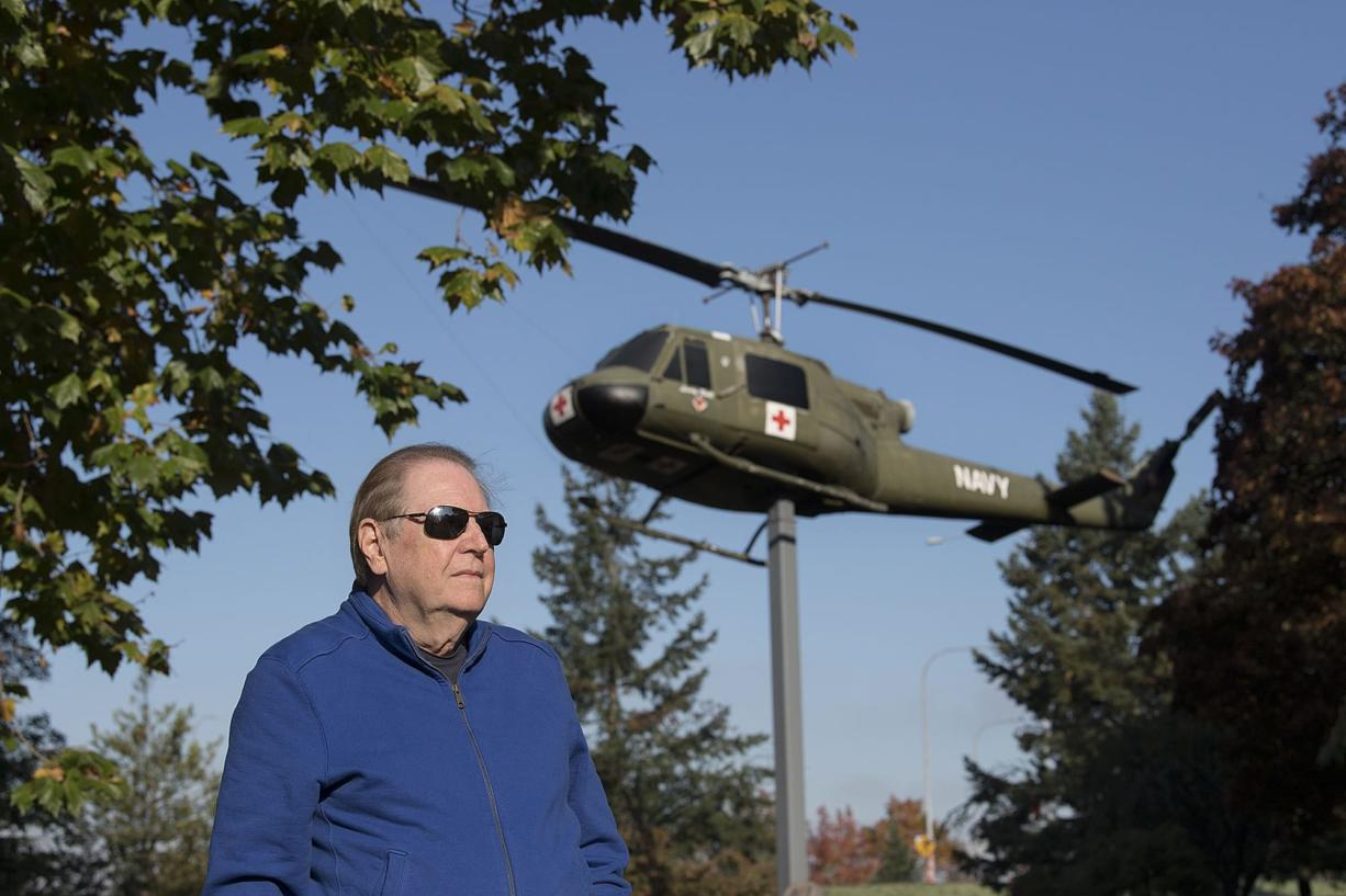 """Vietnam War veteran Jim Voorhees pauses for a portrait with a Vietnam-era Huey helicopter named """"Lady Bell"""" at the Vietnam War Memorial on Oct. 25. Voorhees flew two tours as an Army helicopter pilot."""
