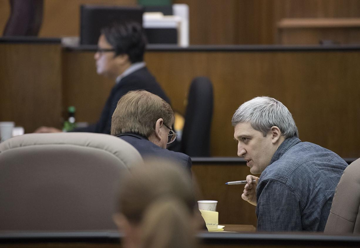 Brent Luyster, right, waits for opening statements to begin in his triple aggravated murder trial in Clark County Superior Court on Nov. 1.