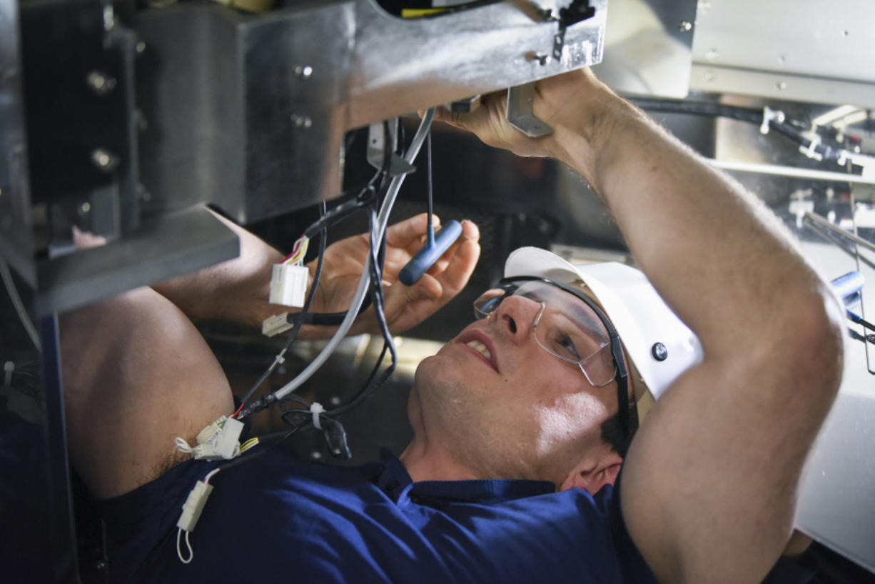 Shane Hoffman, a U.S. Marine Corps veteran, works on removing the motor from a wafer transfer robot in a vertical diffusion furnace at Kokusai in Vancouver. Hoffman is one of many military veterans hired by the company as it looks to set record revenues this year.