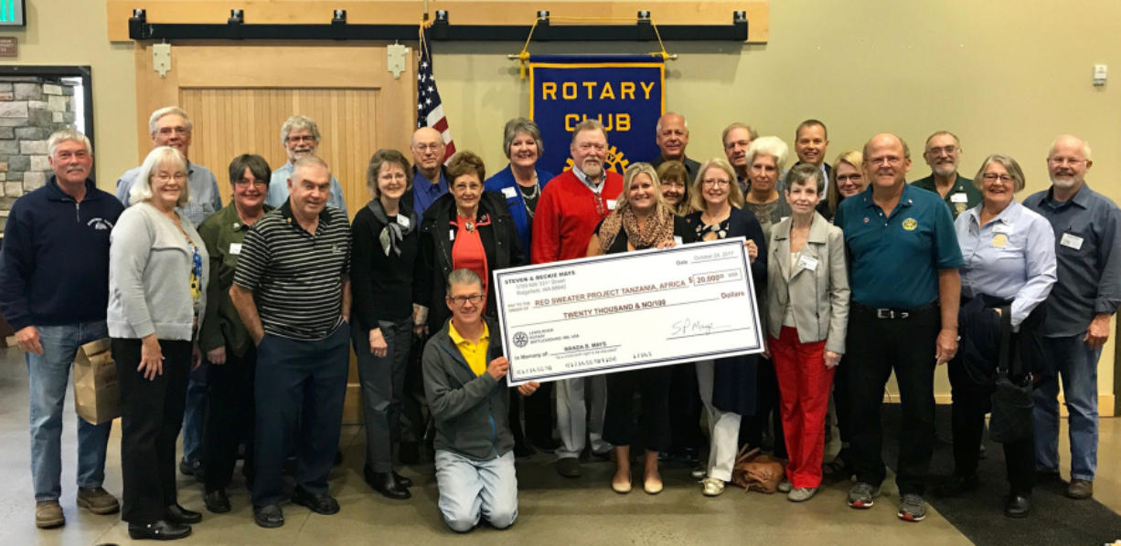 Battle Ground: Members of the Lewis River Rotary present a check for $20,000 to Ashley Homer, center, director of the Red Sweater Project, a nonprofit which looks to help kids in Tanzania continue education after elementary school.