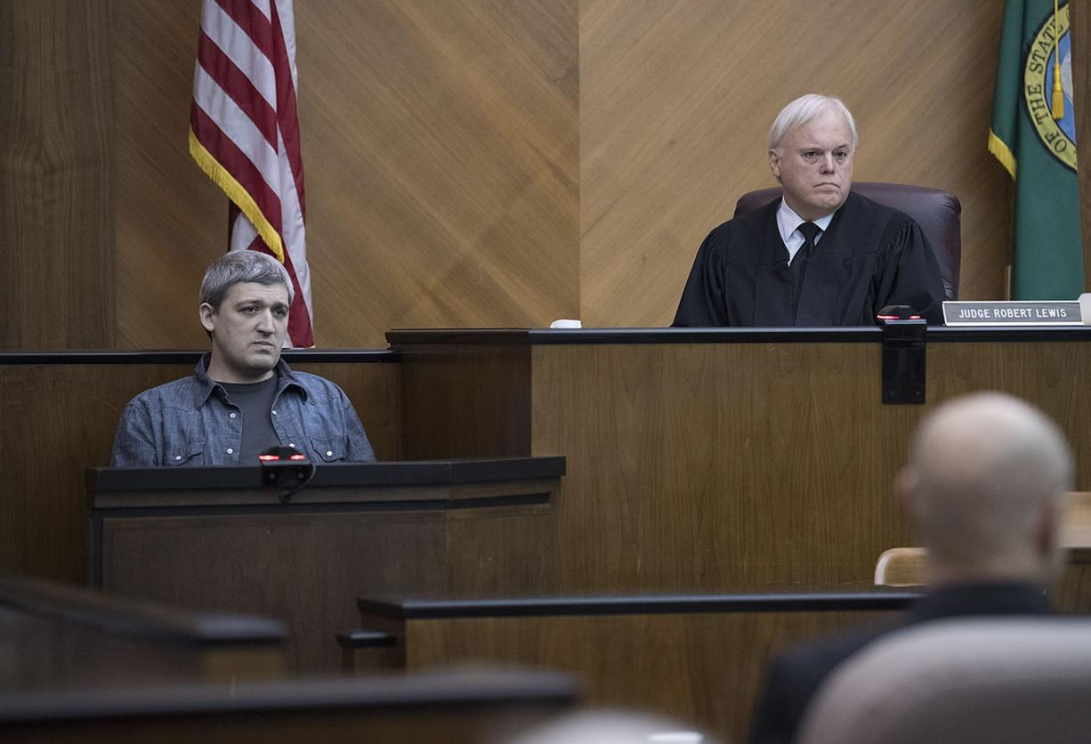 Brent Luyster, left, takes the stand during his triple aggravated murder trial as Judge Robert Lewis listens in Clark County Superior Court on Tuesday morning.